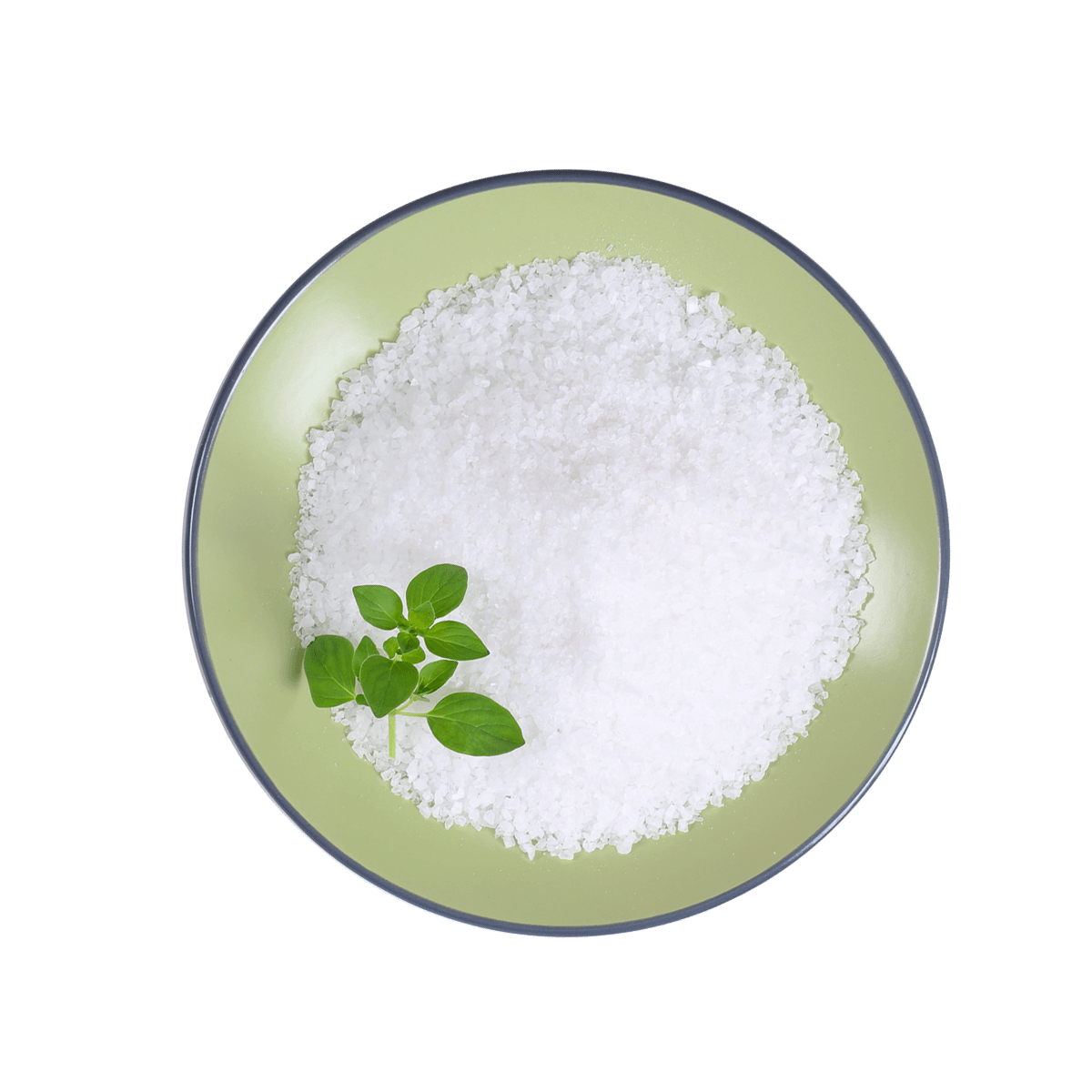 Light green bowl filled with coarse salt granules and natural green leaves combined with Iodine to make Potassium Iodide.